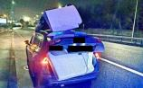 Ah shur it'll be grand! Gardaí stop car with couch perched on roof